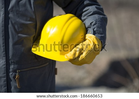 hand of worker with yellow hard-hat,natural light #186660653