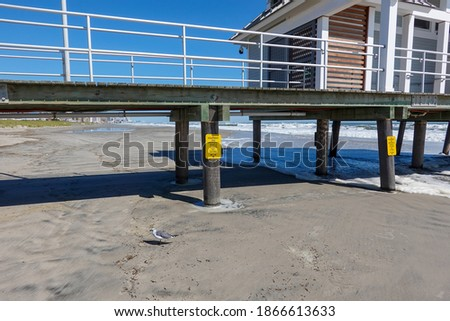 Wooden pier on thick piles on wet beach sand with a building on top of the boardwalk. There are yellow signs on the supports #1866613633