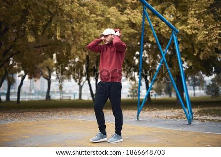 Athletic sporty man training in hoodie sweatshirt in urban city park  basketball court.