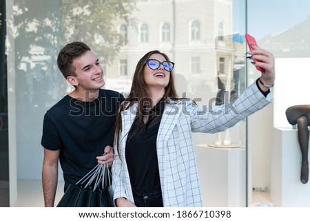 Young couple in stylish clothes makes selfie. Girl photographs herself against her boyfriend.