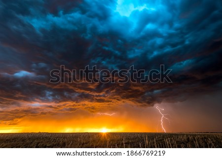 A nighttime, tornadic mezocyclone lightning storm shoots bolt of electricity to the ground and lights up the field and dirt road in Tornado Alley. Royalty-Free Stock Photo #1866769219