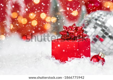 Banner. Christmas red gift box in a red snowy landscape on a bokeh background. Space for text. The concept of the delivery of gifts and greetings card happy New year. Close up. #1866775942