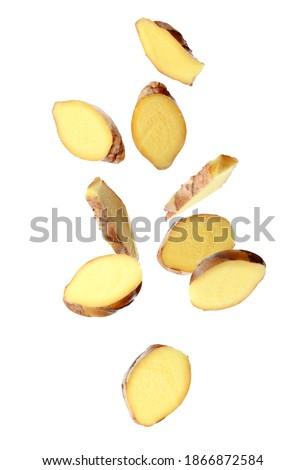 Fresh sliced ginger falling on white background Royalty-Free Stock Photo #1866872584