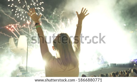 Young happy woman enjoying fireworks in the night sky on New Year's Eve in Singapore. Nightlife, party or open air. Leisure activity, entertainment, Christmas celebration concept. Royalty-Free Stock Photo #1866880771