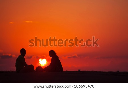 Silhouette of a loving couple, who sits on a sandy ocean beach at sunset and meditating #186693470