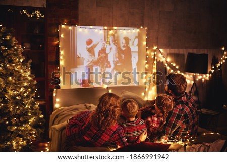 happy family in checkered pajamas: mother father and children watching projector, film, movies with popcorn in christmas holiday evening   at home 