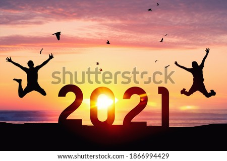 Silhouette men jumping and birds flying on sunset sky at top of mountain and number like 2021 abstract background. Happy new year and holiday celebration concept. Vintage tone filter color style. Royalty-Free Stock Photo #1866994429