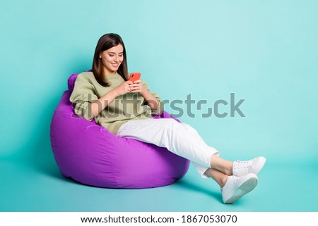 Photo portrait full body view of smiling girl chatting holding phone in two hands sitting in beanbag chair isolated on vivid turquoise colored background Royalty-Free Stock Photo #1867053070