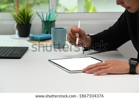 Cropped shot of a graphic designer editing some picture with digital tablet on white desk.
