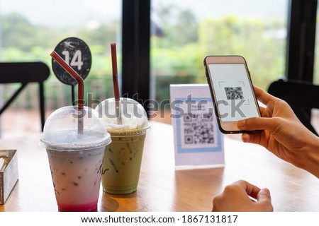Women's hands are using  the phone to scan the qr code to select food menu. Scan to get discounts or pay for food. The concept of using a phone to transfer money or paying money online without cash. Royalty-Free Stock Photo #1867131817