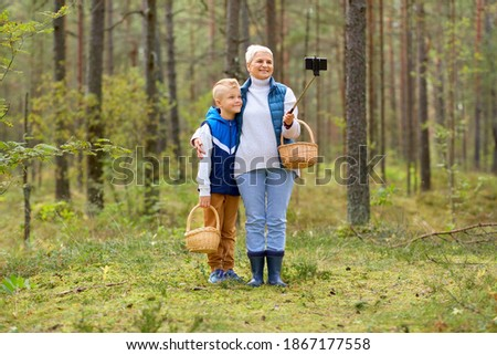 picking season, leisure and people concept - happy smiling grandmother and grandson with mushrooms in baskets taking picture with smartphone on selfie stick in forest