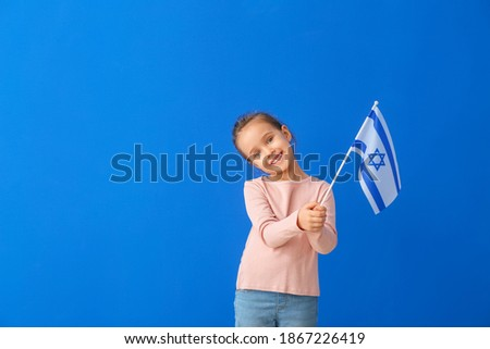 Little girl with the flag of Israel on color background Royalty-Free Stock Photo #1867226419