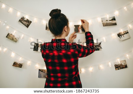 Young beautiful woman hangs a photos on a garland with light on the wall. Bokeh, girl in red checkered shirt, comfort at home, New Year's mood, Christmas decorations. Royalty-Free Stock Photo #1867243735