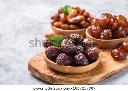 Dates or dattes palm fruit in wooden bowl is snack healthy. Royalty-Free Stock Photo #1867259989
