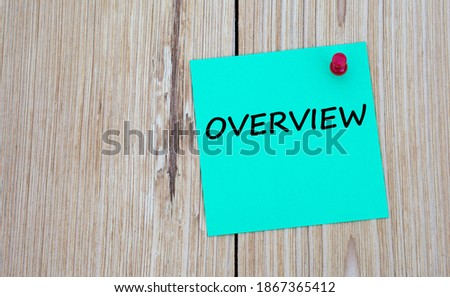 OVERVIEW - word written on a green sheet for notes, which is pinned to a light wooden board. Business concept Royalty-Free Stock Photo #1867365412