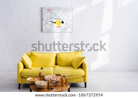 spacious living room with yellow sofa, picture on white wall, table with delicious pizza, beer, chips and popcorn in bowls