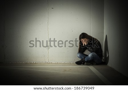 Depressed teenage girl with hands over face sitting in the corner. #186739049