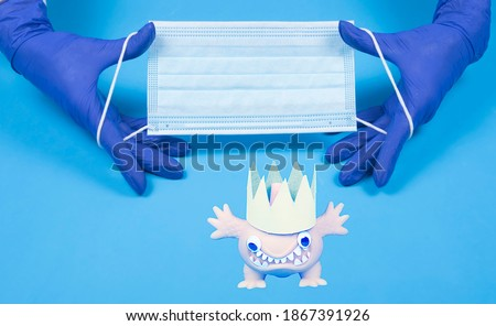 Doctor's hands holding medical mask and image of coronavirus on blue background top view with copy space. Hands in gloves hold cloth mask flat lay with mockup.