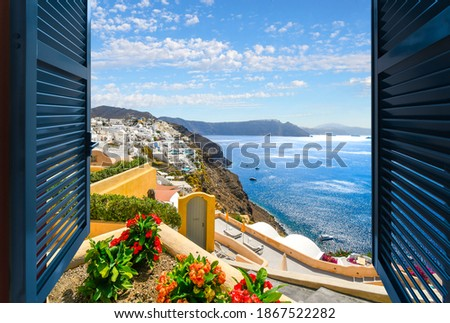 View through an open window of the Aegean Sea, caldera and town of Oia and Thira on the island of Santorini Greece. Royalty-Free Stock Photo #1867522282