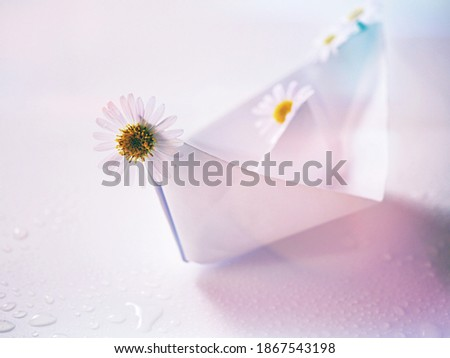 White paper boat with daisy flower on white background