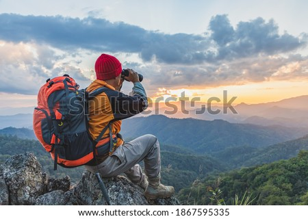 Hikers with backpacks holding binoculars sitting on top of the rock mountain Royalty-Free Stock Photo #1867595335