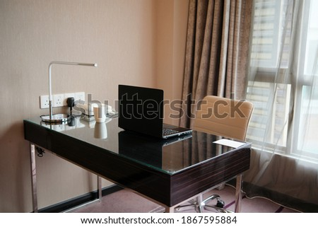 Hotel room work desk with black laptop, white cup, table lamp and telephone Royalty-Free Stock Photo #1867595884