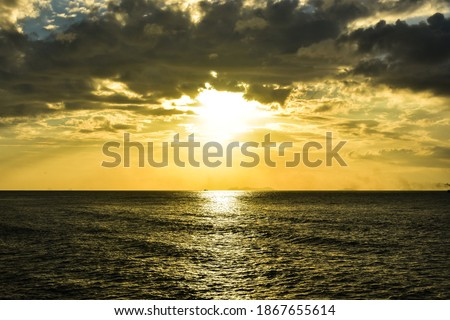 Beautiful sunbeam from sunset under overcast clouds that over calm sea at tropical island. Sunlight reflection. Scenic seascape in the evening at beachfront in Lipa Noi beach, Samui island, Thailand. Royalty-Free Stock Photo #1867655614