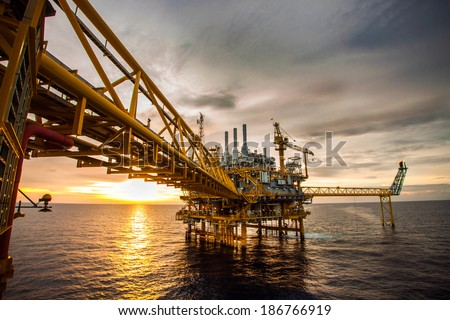 Offshore oil and rig platform in sunset or sunrise time. Construction of production process in the sea. Power energy of the world. Royalty-Free Stock Photo #186766919