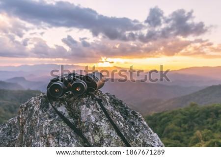 binoculars on top of rock mountain at sunset Royalty-Free Stock Photo #1867671289