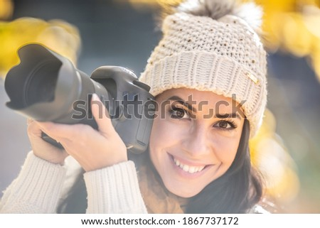 Smiling good-looking female photographer in a pompom hat takes pictures outside on a sunny fall day.