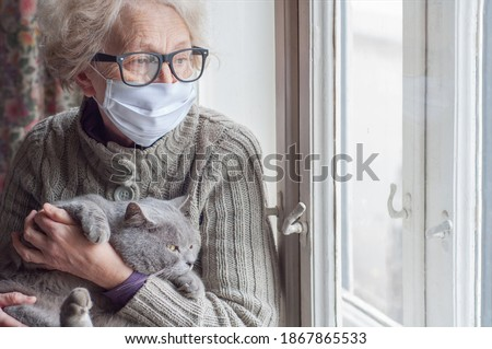 Elderly woman in protective mask holding a cat looks out the window wearing. Christmas quarantine covid19. Coronavirus epidemic. Waiting. Depression. Insulation at home. Pets save you from loneliness Royalty-Free Stock Photo #1867865533
