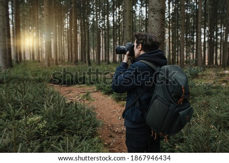 The tourist takes a picture with his camera on his trip in a beautiful forest at sunset. A small hiking trail conifers and fir trees.