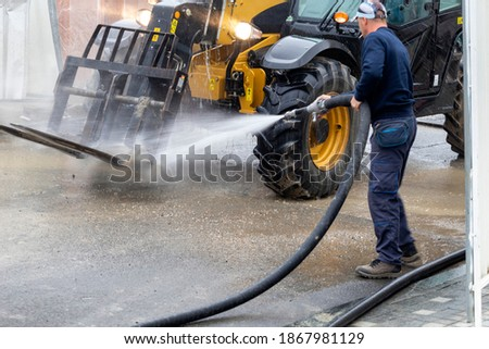 Washing construction machinery off dirt before goes out of the construction site. High pressured water washing. Selective focus. Royalty-Free Stock Photo #1867981129