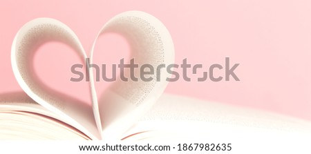 Book pages in shape of heart on pink background. Love, valentines or mother's day concept. Close up, copy space. Royalty-Free Stock Photo #1867982635