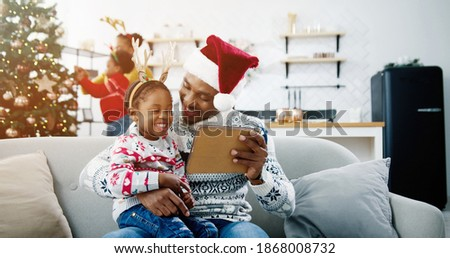 Close up of happy African American little kid sitting with dad in santa hat at decorated room and watching cartoons on tablet. Mom and child decorating Christmas tree on background. Xmas concept