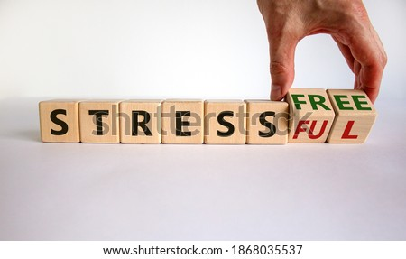 Stress-free or stressful symbol. Hand turns cubes and changes the words 'stressful' to 'stress-free'. Beautiful white background. Copy space, business and stress-free or stressful concept. #1868035537