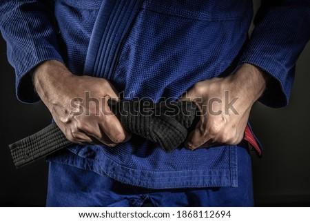Close up on hand of unknown caucasian man holding brazilian jiu jitsu bjj black belt around his waist while wearing kimono gi in dark - martial arts mastery skill and confidence achievement concept Royalty-Free Stock Photo #1868112694