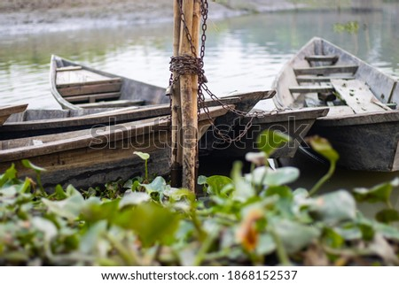 Parked small wooden boats with iron chain beside the river