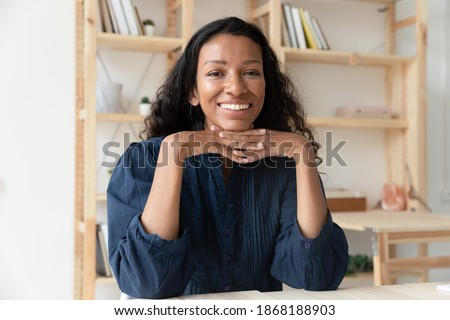 Portrait of smiling biracial young woman talk video call with client or customer at workplace. Happy African American female have webcam digital virtual conference in office, use modern technologies.