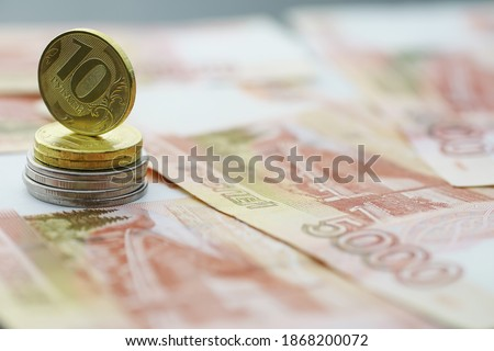 """Russian banknotes and coins """"rubles."""" Banknote with inscription """"five thousand rubles"""" and coins of 5 and 10 rubles. Background made of money. Royalty-Free Stock Photo #1868200072"""