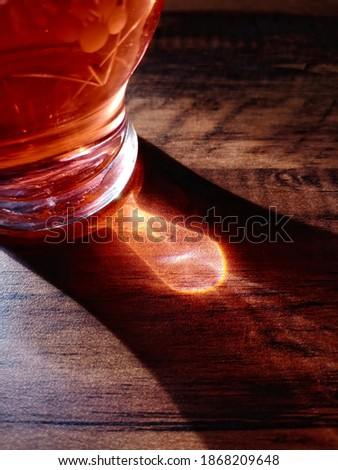 The shadow from the light reflection of a glass of black tea, by the sunrise, in the morning. Forms an abstrack shape. beautiful and amazing picture. Clear and brown,  on the wooden table. Silhouette