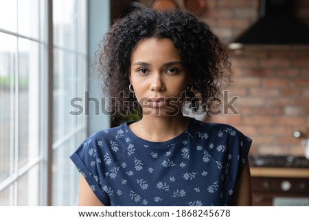 Head shot portrait of young serious african american woman standing in own apartment. Beautiful millennial mixed race lady looking at camera, feeling thoughtful alone at home, posing for photo. Royalty-Free Stock Photo #1868245678
