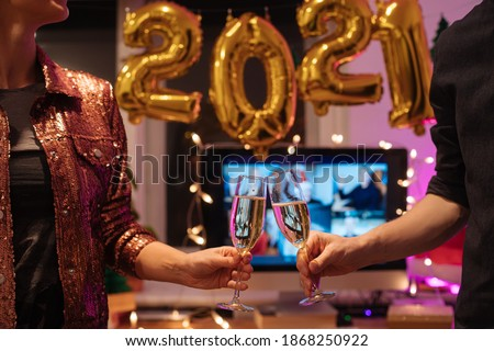 Celebrating Virtual Christmas New Year's Eve party 2021 at home during Covid-19 pandemic. Couple holding and toasting champagne glasses How to celebrate and decorate foiled balloons of 2021.  Royalty-Free Stock Photo #1868250922