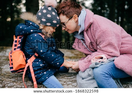 picture of lovely young caucasian female with pretty face, short dark hair, big eyes sits on the felled trees with her child in a forest