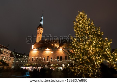 Estonian old medieval town square called Raekoja Plats. Christmas market and decorated  christmas tree. Alot of light pollution in the air. Winter with out any snow - climate change. Slow shutter pic