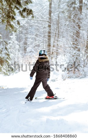little child skiing in winter slope among trees