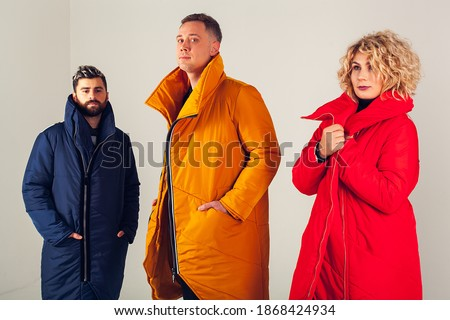 Three models on a white background in warm, winter down jackets. A group photo of two men and one woman wearing colorful clothes on a white background. Stylish winter clothes  Royalty-Free Stock Photo #1868424934