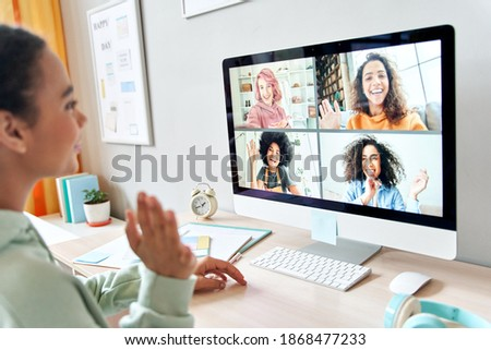 Mixed race teen girl waving talking to happy diverse teenage friends during online virtual chat video call in group conference distance chat virtual meeting using computer at home. Over shoulder view. Royalty-Free Stock Photo #1868477233