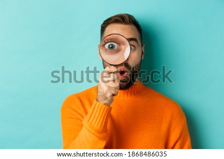 Funny man looking through magnifying glass, searching or investigating something, standing in orange sweater against turquoise background Royalty-Free Stock Photo #1868486035