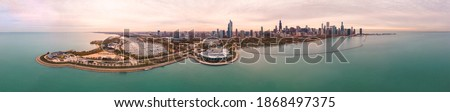 Incredible wide angle Chicago city skyline aerial panorama over Lake Michigan with highrise skyscraper buildings and boat harbors along the horizon with a beautiful orange and blue sunset sky above. Royalty-Free Stock Photo #1868497375